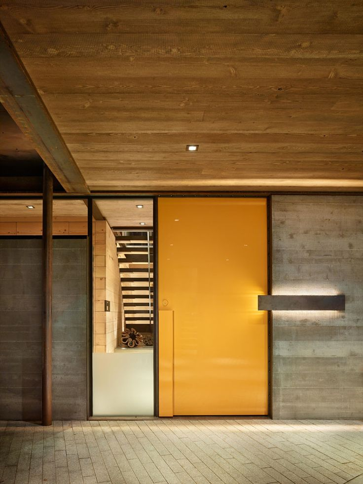 This modern industrial house has a briight yellow front door to greet you and a window gives you a glimpse into the home.