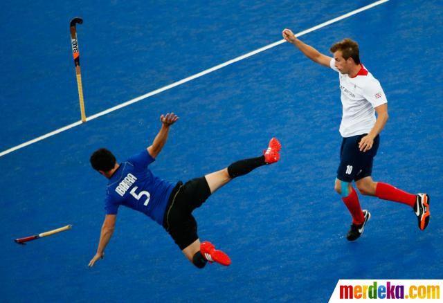 Pemain Argentina Pedro Ibarra terjatuh saat bertanding melawan Inggris di pertandingan Hoki.