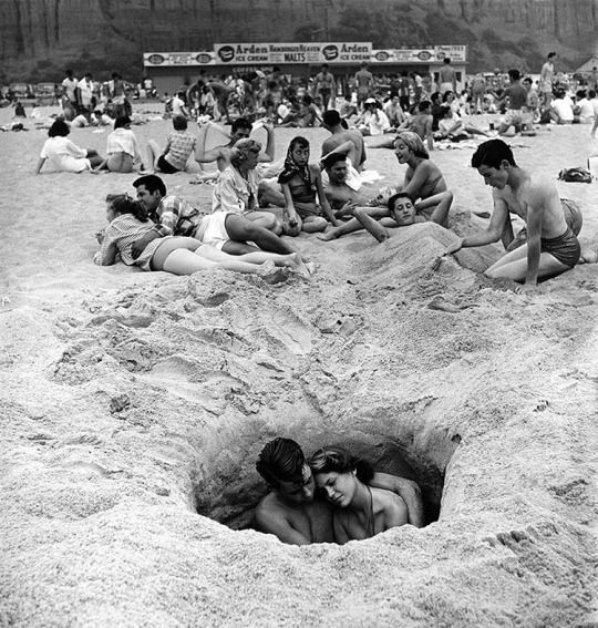 Surrounded by others, a couple enjoys some privacy as they embrace in a hole in the sand on a beach in Santa Monica, California, July 4, 1950. (Ralph Crane—The LIFE Images Collection/Getty Images) #1950s #Summer #California