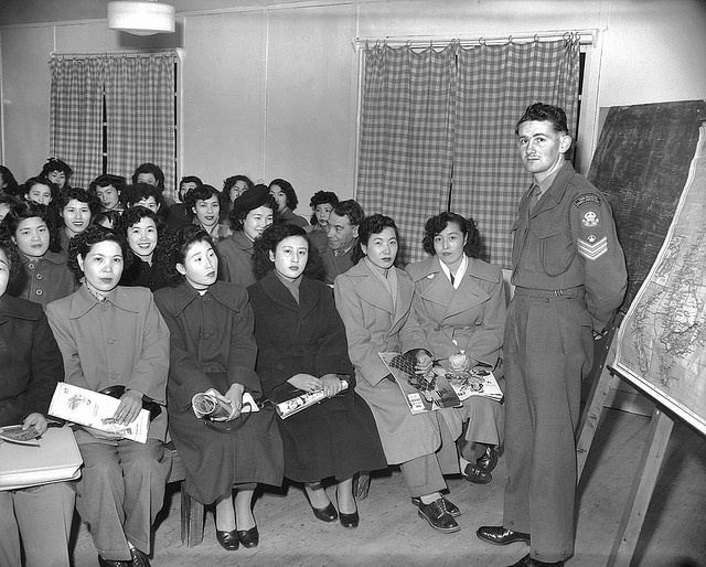 War brides learn about Australia, 1952   Sergeant T. R. MacQuin of Australian Army Education Service stands in front of a class of Japanese war brides to give them information about Australia.