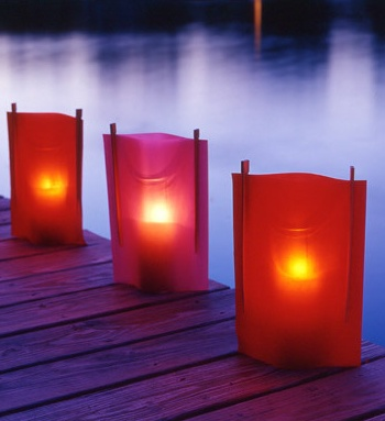 Colorful sheets of vellum paper sandwiching tall votive candles in glass holders with chopsticks