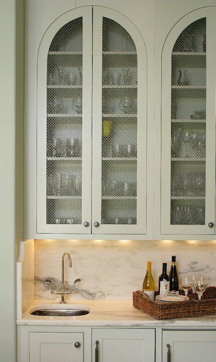 great butlers pantry with arched upper cabinet doors & inset grates, white marble back splash and counters, under-mount prep sink and gooseneck faucet.