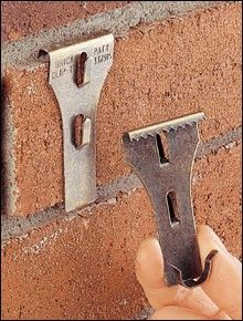 Brick Clips - hanging on brick without drilling.  Great for hanging stuff on the outside wall, or inside brick walls or fireplaces.