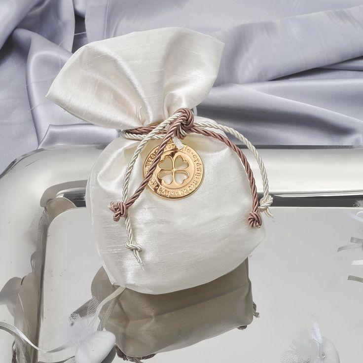 Μπομπονιέρα πουγκί σαντούκ με διπλό κορδόνι και ροζ χρυσό αντικείμενο, στρογγυλό με καρδιές και ευχές και 5 κουφέτα Χατζηγιαννάκη. Η τιμή είναι ενδεικτική και καθορίζεται από την ποσότητα.