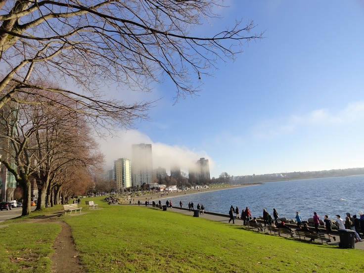 People enjoying Vancouver Spring weather are walking the Seawall in English Bay (at the entrance of Stanley Park)