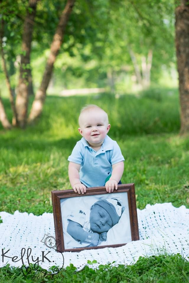 One year old, with baby picture from the hospital. This would be a good idea to take a picture of every year with the previous year's picture as the one they're holding!