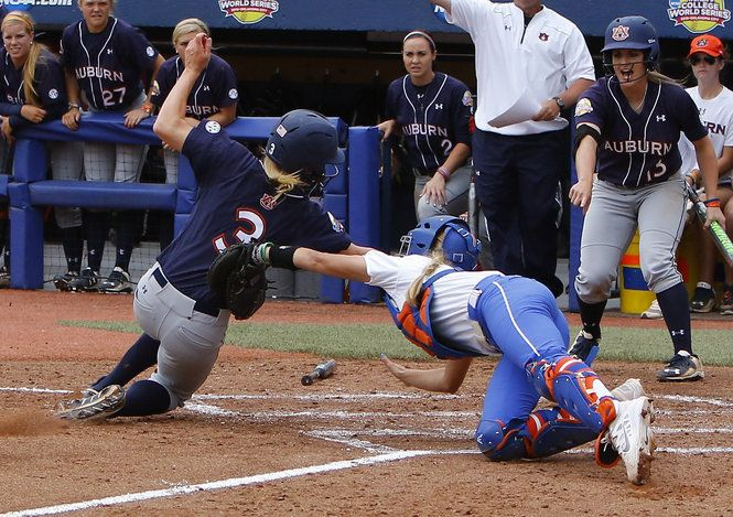 Florida catcher Aubrey Munro, right, tags out Auburn's Morgan Estell, left, in the second inning during an NCAA Women's College World Series softball game in Oklahoma City, Sunday, May 31, 2015