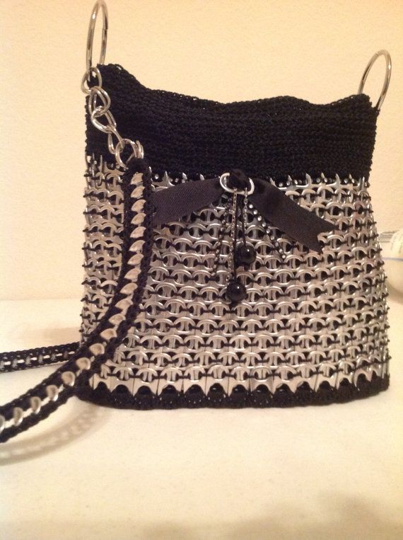 Black pop Tab Purse with zipper closure. Has black lining with one large pocket with velcro. It measures 10 wide and 9.5 tall, has a chain and pop tab shoulder strap. Made out of nylon crochet thread, can be hand washed and set out to dry. This purse is great for everyday use and what an awesome conversation piece to add to your wardrobe. Thanks for shopping