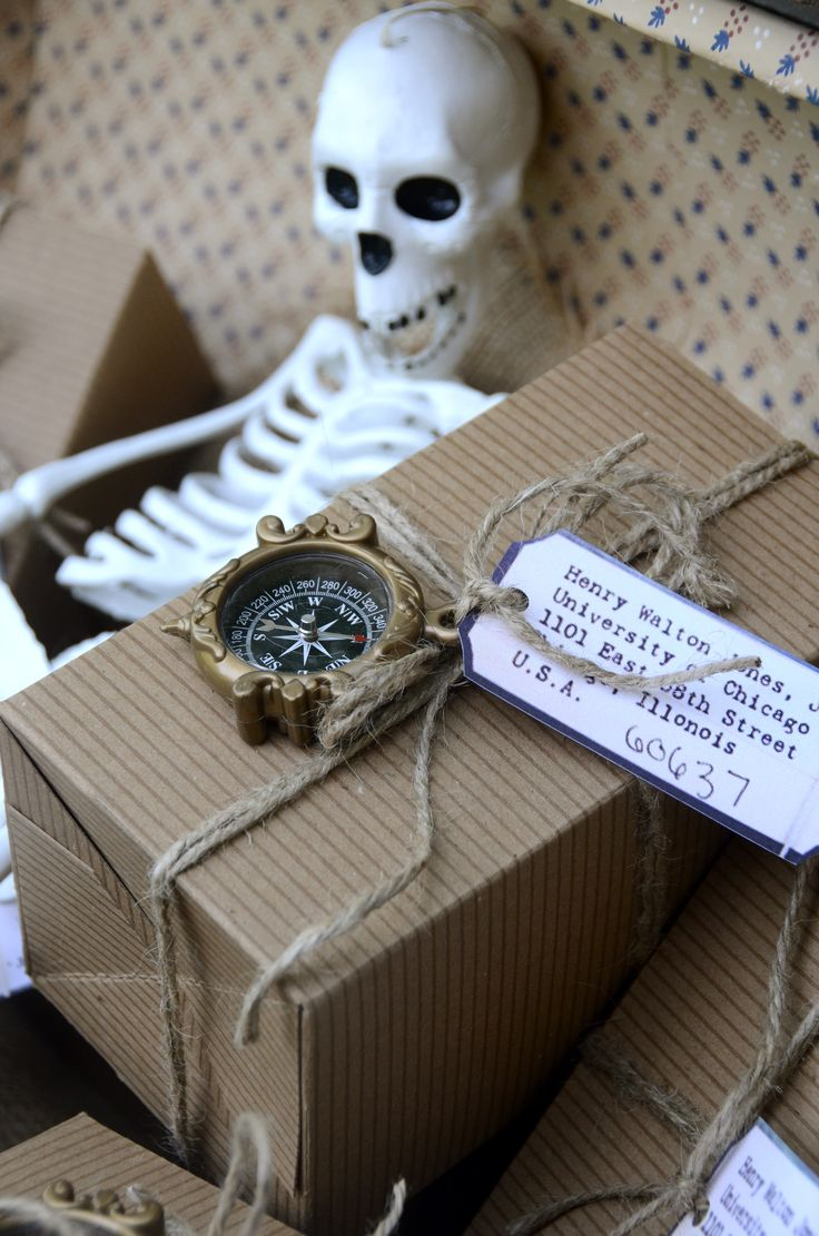 Indiana Jones: Party favor featuring Dr. Jones tag and compass. Inside is crate packing material and gold foil wrapped candies.