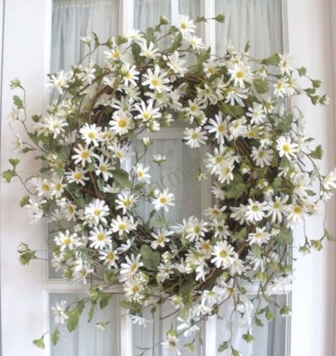 This daisy wreath would be so pretty hung on the front of the ceremony entrance door.    While one wouldn't want to bang a nail in a door, wide satin ribbon could be attached to wreath and then, using thumb nails, attached to door along the very top upper area.