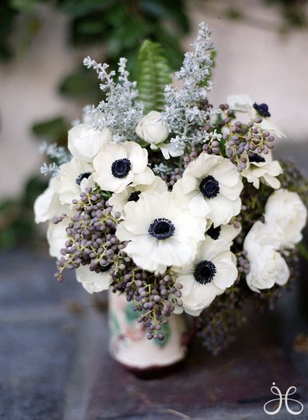 This breathtakingly unique bridal bouquet is made of huckleberry, french anemones, and sword fern, and clasped with a fern frond brooch.