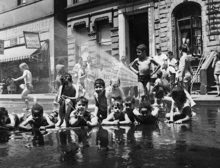 23 Vintage Photos That Show What Summer Fun Looked Like Before The Internet --- July 17, 1954: A street hydrant provides an impromptu bath for a group of children when temperatures in New York climb above the 90's. (Photo by Keystone/Getty Images)