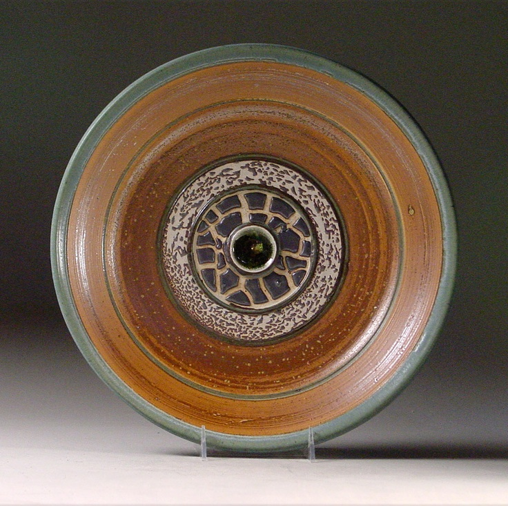 """Ocean Sediment Glazes by Joan Lederman.       Plates Spread & Collide While Gulf of Mexico Evolves.    Words written on back say, """"Center of sea glass contains volcanic sand from Antarctica, Iceland and Hawaii is framed by Earth crust drillings (SPREADING) from mid-Atlantic Ridge framed by accretionary prism (COLLIDING) sediment. Tectonic plates.""""    Back around foot says, """"sediment glazes from Gulf of Mexico 1998 and 2009 . . . """""""
