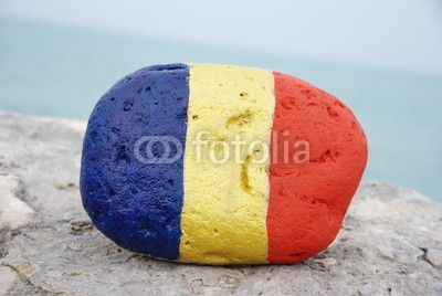 Romanian flag painted on a stone with sea background