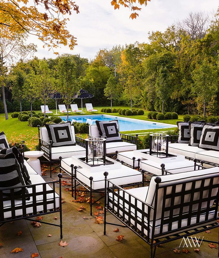 Chic Patio Features Wrought Iron Sofas, Chairs And Ottomans Covered In Black  And White Cushions Placed In Front Of The In Ground Pool.
