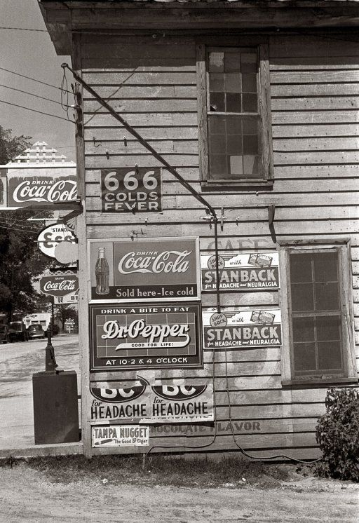 April 1938. Store in Halifax, North Carolina, with signs advertising carbonated beverages and patent medicines.