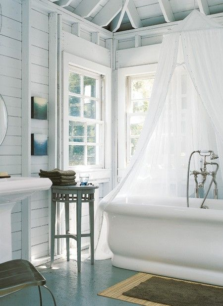 Romantic Cottage Bathroom: Antique furniture in warm blue-green shades and a softly draping curtain add romance and country charm.      Wood walls and a rustic ceiling, both painted a fresh vintage white, brighten a cottage bathroom with beautiful windows, fixtures and natural light.
