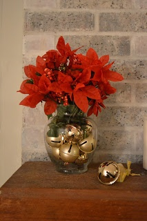 Easy Christmas decor= fill a clear vase with jingle bells and add a bouquet of bright red poinsettias