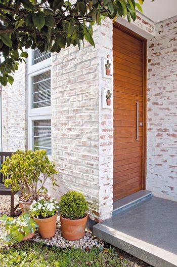 Para dar um efeito descascado na parede, tijolos de barro foram pintados com tinta branca e depois lixados.