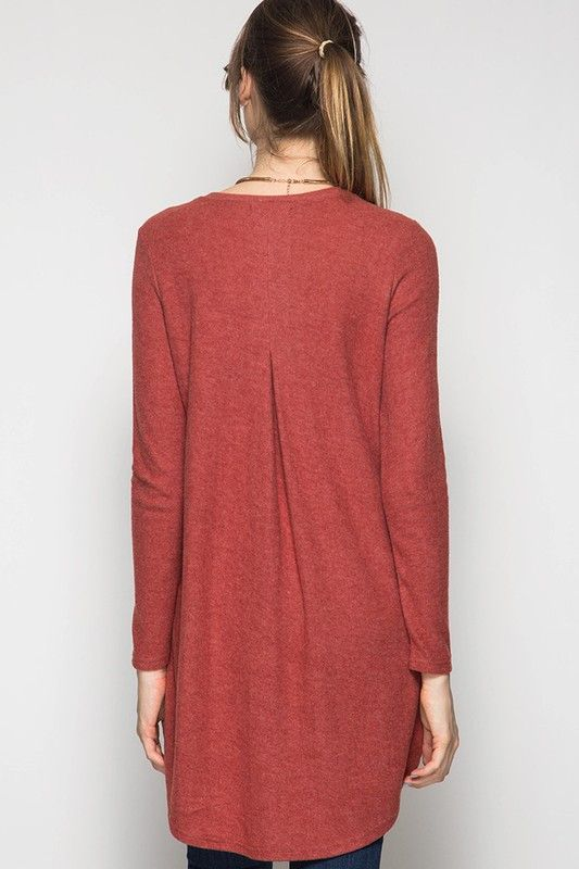 A unique twist on the long sleeve tunic! Features a tulip front overlapping detail, back pleat, and high-low fit. 60% Cotton 40% Rayon This is a pre-order style, expected to ship during the first week