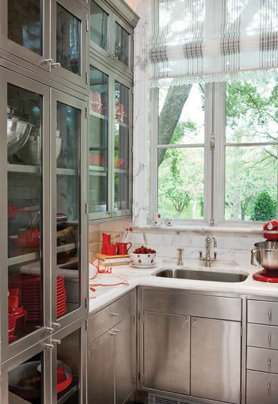 stainless cabinets softened by the traditional styling, marble counters and lots of light