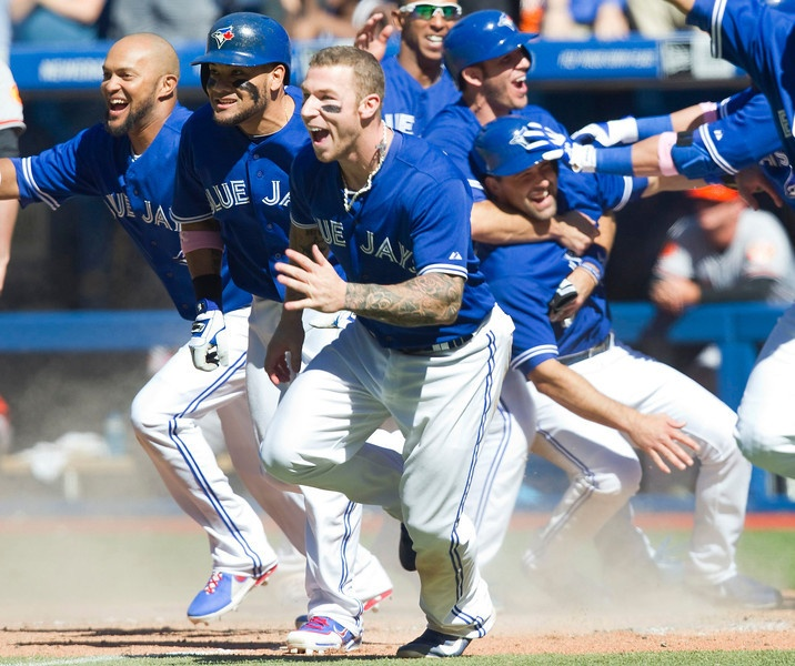 Toronto Blue Jays players Brett Lawrie (C), Emillio Bonafacio (L) and Melky Cabrera run on to the field to celebrate with team mate Munenori Kawasaki who hit a game winning double in the ninth inning of their American League MLB baseball game against the Baltimore Orioles in Toronto May 26, 2013. Jays J.P. Arencibia and Mark Derosa in the rear right of the photo scored the tying and winning runs on Kawasakis hit. REUTERS/Fred Thornhill