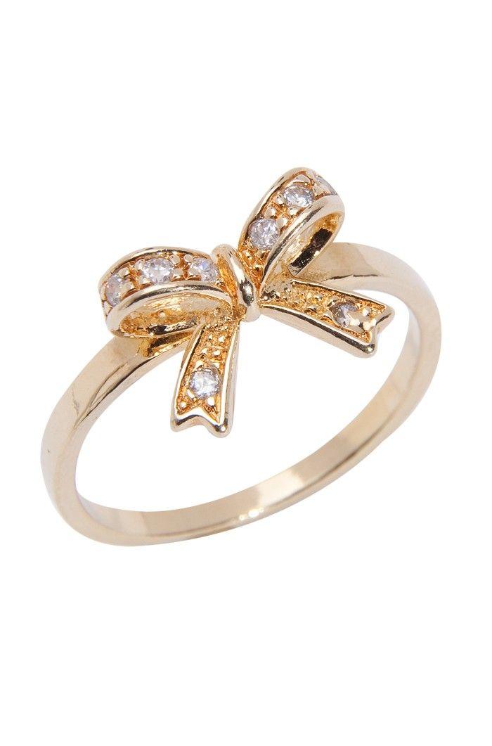 Banhado a ouro, o destaque do anel é o laço, que dá um ar super-romântico ao seu look. A peça tem um efeito lindo e pode ser usada durante o dia com roupas neutras. Você pode combinar com uma pulseira dourada para completar o visual, escolha uma em nossa loja online ou em sua própria coleção. Disponível do tamanho 13 ao 21. Dimensões: Laço 0,7 cm de largura x 1,1 cm de comprimento. Peso: 2,3 gramas.