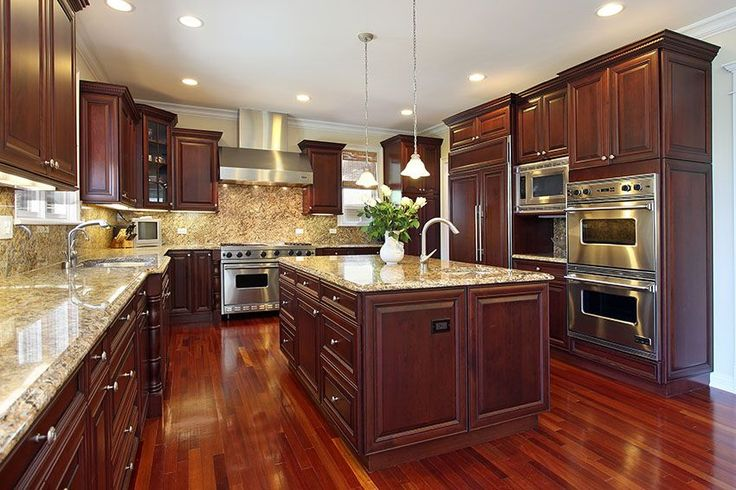Kitchen in luxury home with dark cherry wood cabinetry, wood flooring, and granite island.