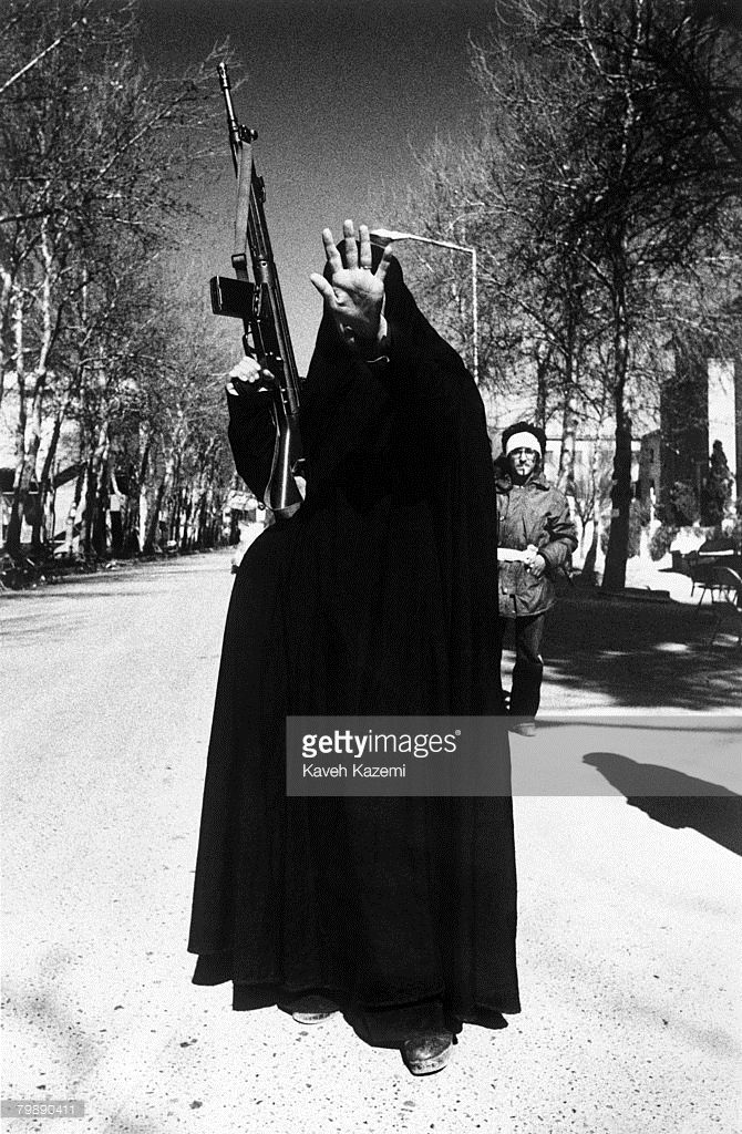 A woman, in black chador and carrying a G-3 machine gun, holds up her hand in a gesture of defiance to the camera, Tehran, 12th February 1979. She is amongst the revolutionary forces occupying Tehran University a day after the victory of Islamic Revolution in Iran led by Ayatollah Ruhollah Khomeini.