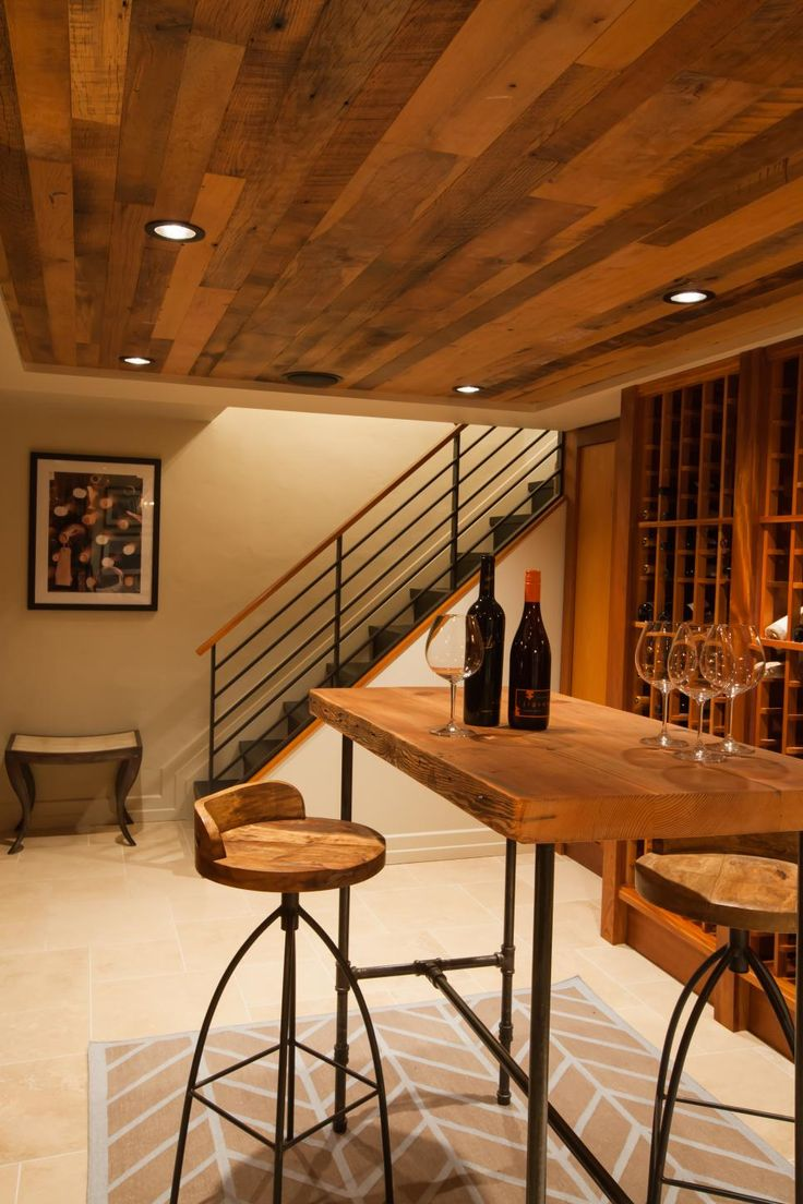 Downstairs, invite guests to a wine tasting in the chic, rustic wine cellar. Pull up a barstool to the counter height table. A wood ceiling perfectly finishes off the space.