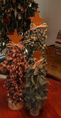 We three trees made out of dowels to desired length, and torn home spun fabric in Christmas colors, a rusty tin star, raffia, and a piece of branch that has been cut on a band saw and drilled in the middle to accommodate dowel for the base.