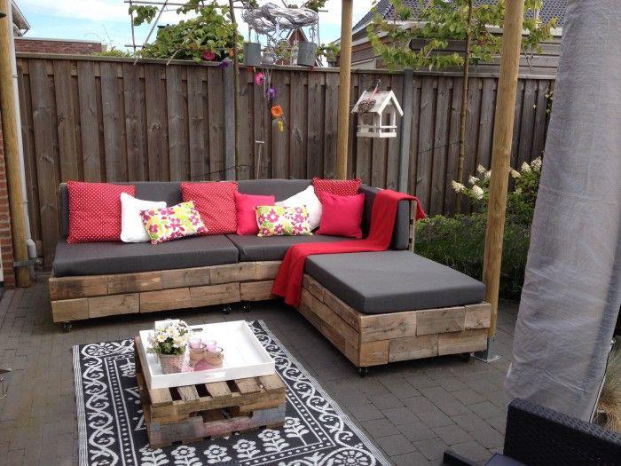 Tuinbank van oude pallets en kussens op maat erbij gemaakt van matrassen