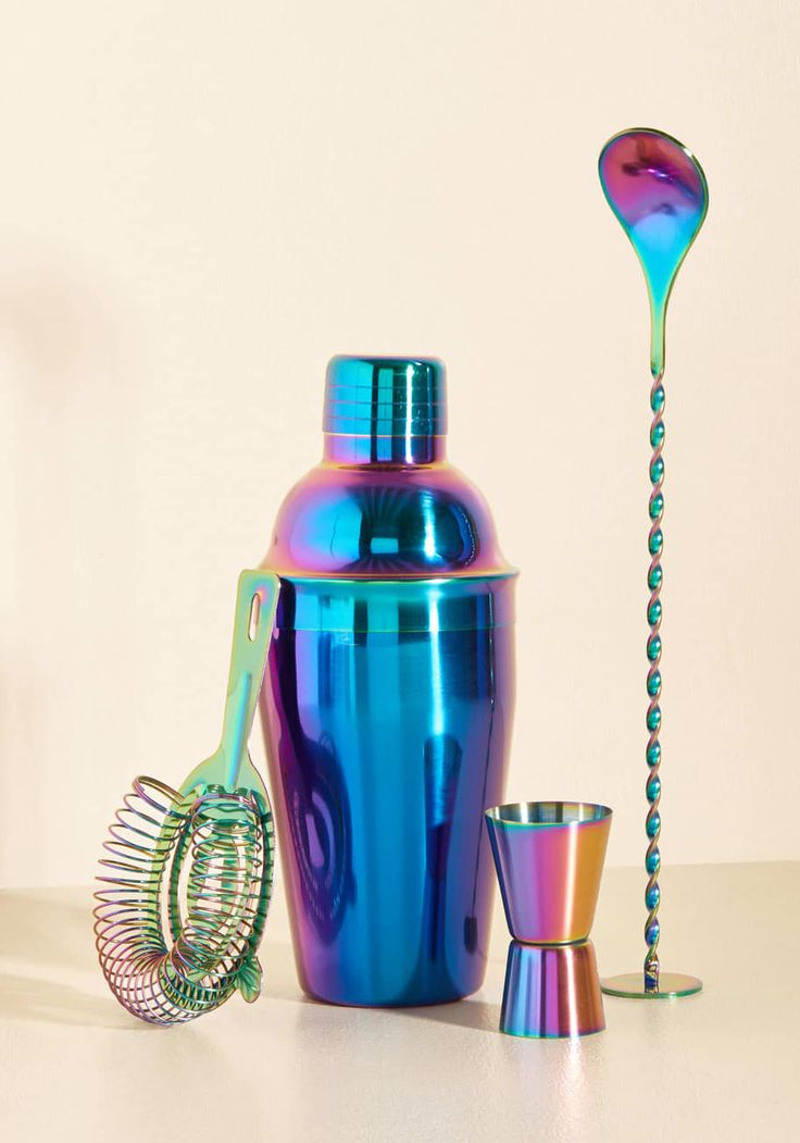 A gorgeous iridescent cocktail shaker set that includes a shaker, strainer, stirrer, and jigger.