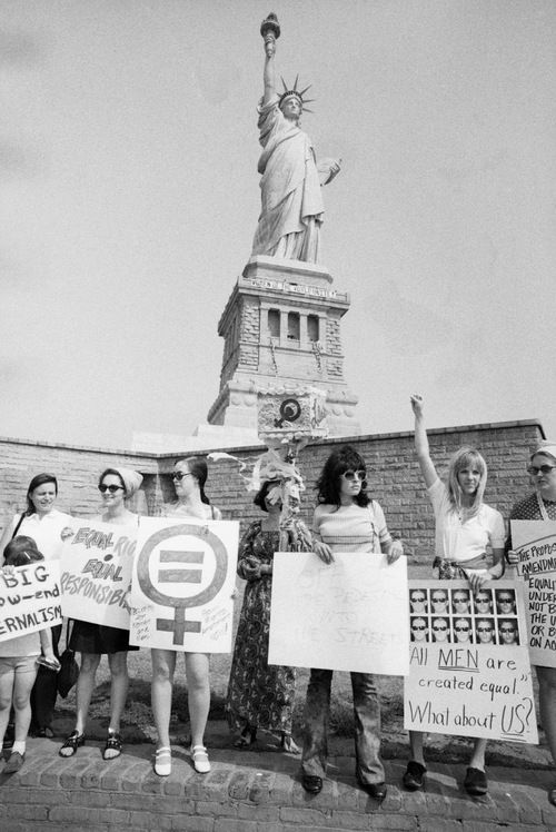Women supporting the Equal Rights Amendment demonstrate in front of the Statue of Liberty on August 10, 1970. (© AP Images)
