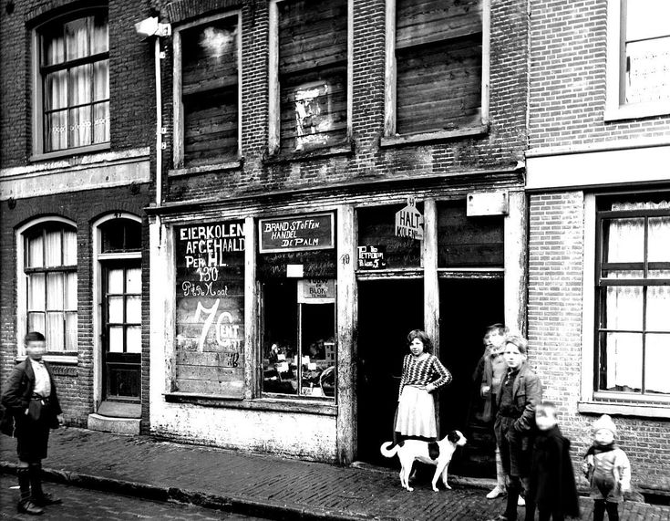 1935. A view of the Palmstraat in the Jordaan neighborhood of Amsterdam. In the center a business specializing in fuel products. The Palmstraat runs between the Lijnbaansgracht and the Brouwersgracht. The dilapidated building illustrates the lack of quality housing in the Jordaan in the 1930's. Over the last 30 years, many of these buildings have been renovated or demolished and replaced by new construction. Photo Stadsarchief Amsterdam / Nico Swaager. #amsterdam #1935 #Palmstraat #Jordaan