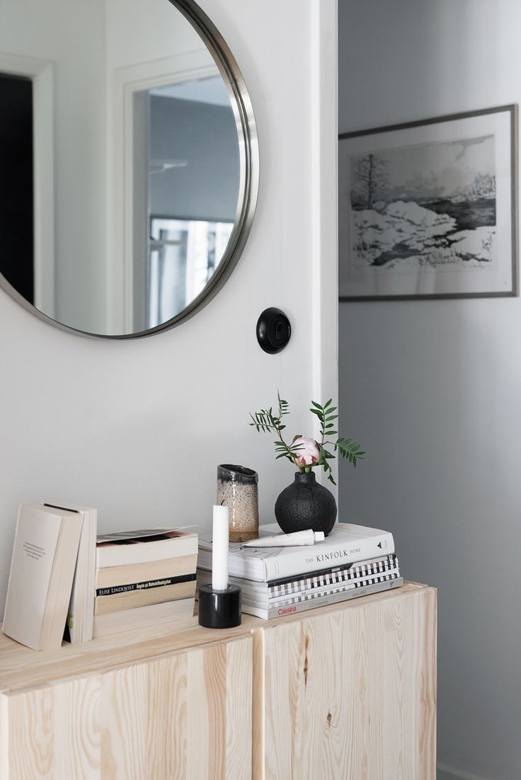 incredibly beautiful round mirror over natural wood chest of drawers