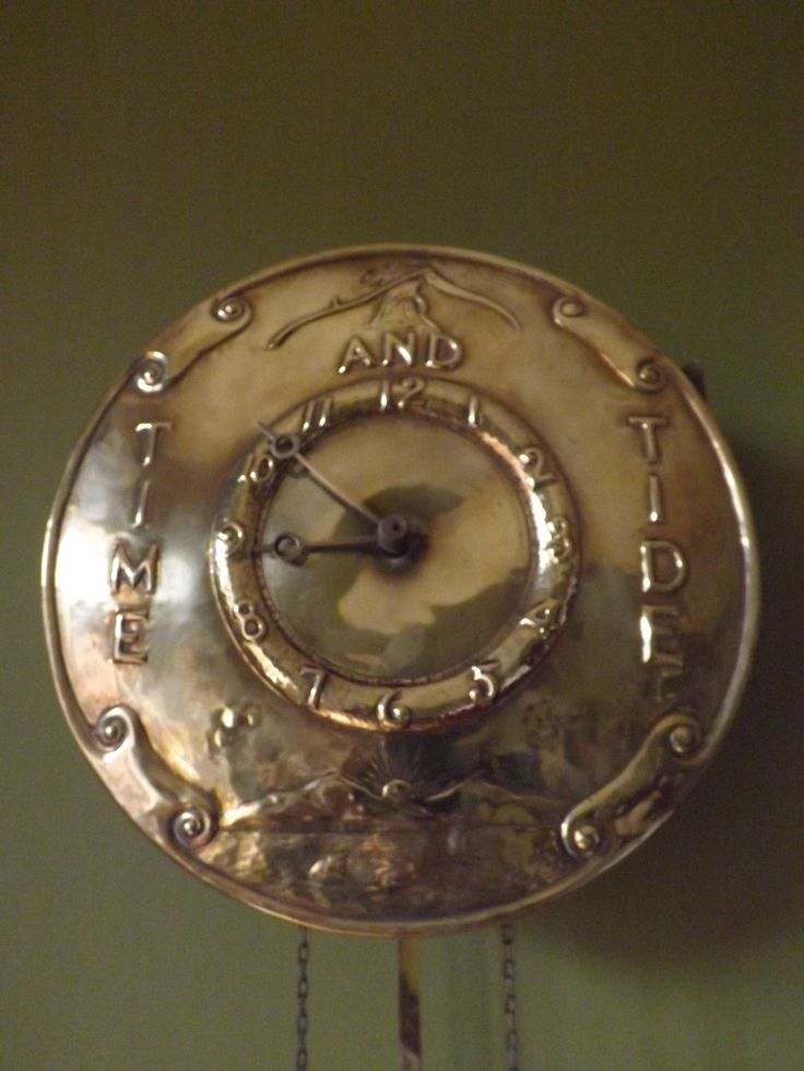 An Arts and Crafts Brass Time and Tide clock  from the Glaswegian school  circa 1900