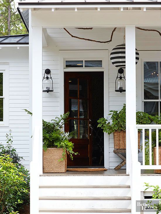 This farmhouse porch beckons you in and extends a warm, yet fresh, welcome, thanks to its punchy black accessories, white facade and gorgeous plantings. Secret to Pretty: Plenty of greenery, proving that plants don't have to be colorful to be impactful. Here, greenery pops against the porch's clean white surfaces creating a modern farmhouse vibe.