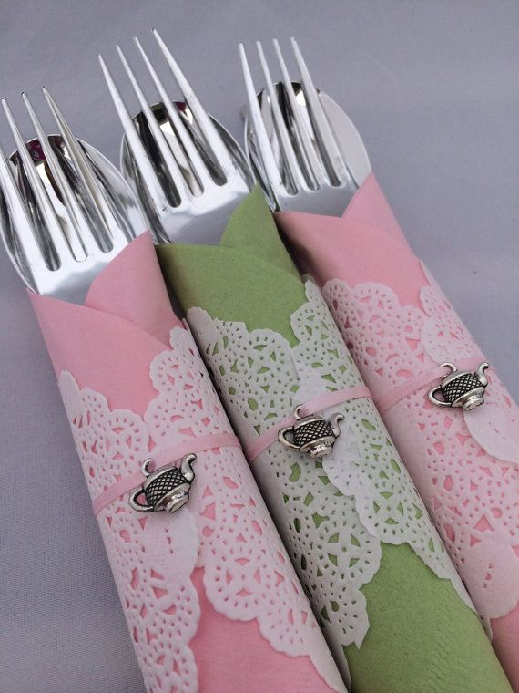 Silver colored plastic knife, fork and spoon decorated with a pretty doily wrapped around a delicate color napkin and hand tied with silver