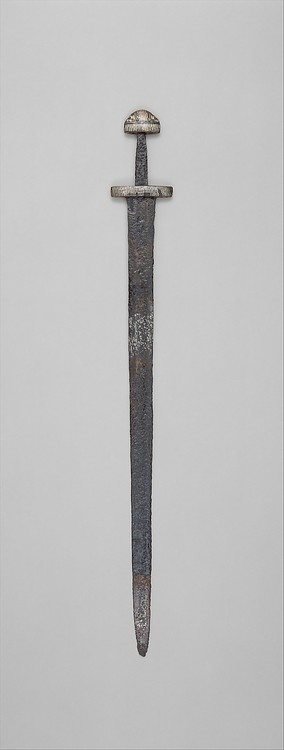 ✯ 10th Century Sword ..Probably Scandinavia.. The skillfully decorated hilt and blade indicate that this sword was carried by a warrior of high rank, perhaps a Viking chieftain or a Frankish nobleman. The braided copper wires on the pommel may represent an earlier Scandinavian custom of tying a talisman to a sword hilt. The pattern-welded blade was forged of intertwined rods of steel and iron, a technique that produced a tough, resilient blade with a distinctive swirling pattern on its…