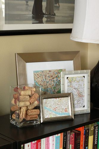 Cute idea...maps of travels in frames....then the corks from the trips in a vase next to them