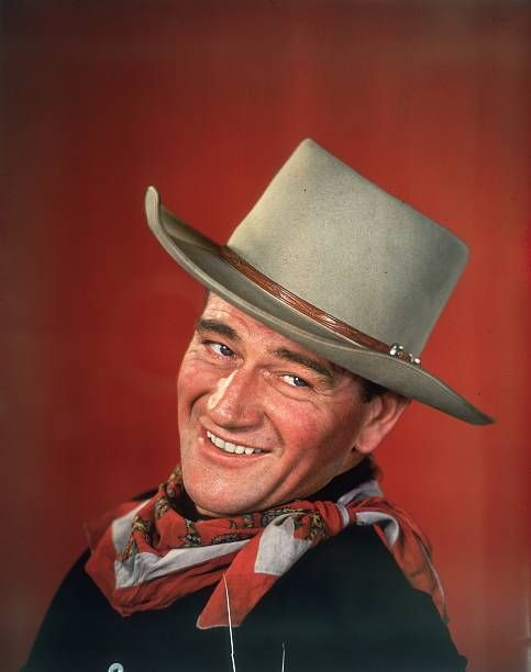 Studio headshot portrait of American actor John Wayne smiling in front of a red background, dressed in Western garb, with his head turned to the side.