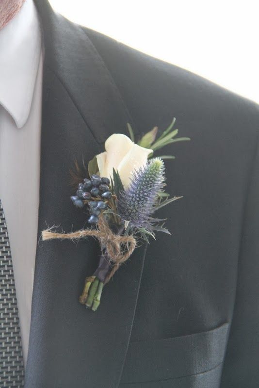 A Beautiful Boutonniere with an Akito Rose, Rosemary, Thistle and Viburnum Tinus, bound with deep blue Ribbon and tied up with earth jute