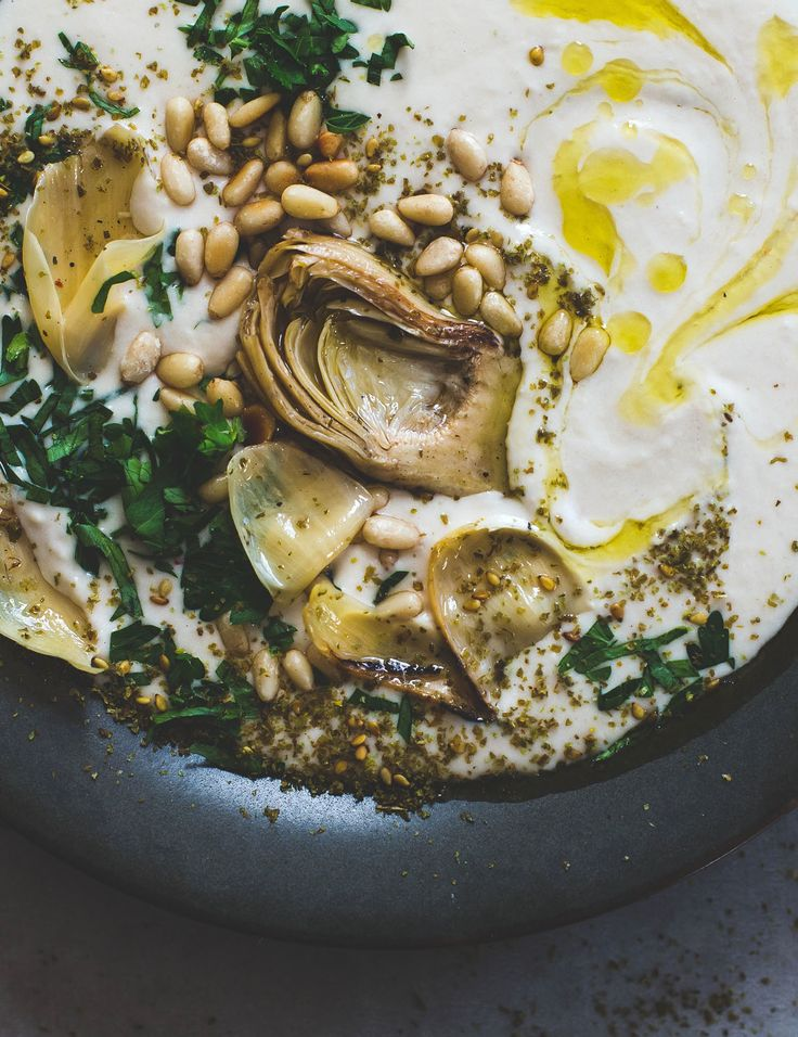 The secret to silky smooth white bean hummus that outshines hummus is revealed. Topped with mediterranean inspired artichokes, pine nuts, olive oil.
