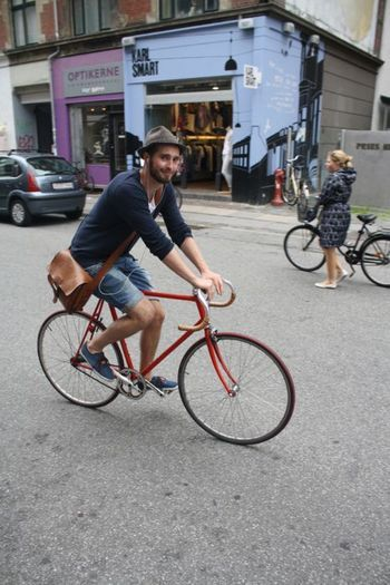ロード用自転車に乗ったヒップスターファッションの男性です。イヤホンで音楽を聴いているようです。