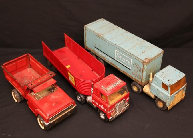 "Metal Structo toy trucks incl one marked ""Structo Hydraulic Dumper"" having locking dump bed and swinging tailgate 14""L, ""Sears"" trailer with ""International"" truck marked ""Sears"" 21""L, and ""ERTL"" having removable open trailer marked ""Structo Grain Company Load Limit 48,000 LBS."" with ""International"" truck approx. 21""L."