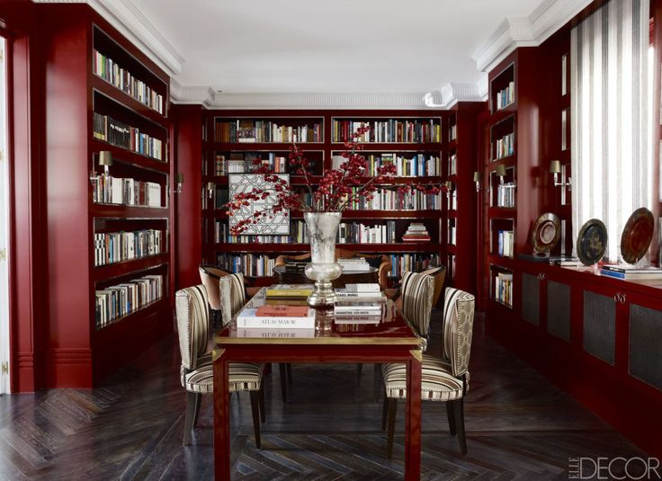In the dining room-cum-library, chairs by Castillo are covered in a cut-velvet stripe by Robert Allen with backs in a Jim Thomson fabric. The lacquer-and-brass table is by Maison Jansen; the walls and bookshelves are painted in Farrow & Ball's Rectory Red.