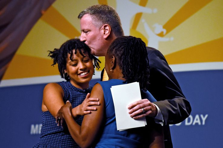 New York City Mayor Bill de Blasio and his wife, Chirlane McCray (R) hug their daughter, Chiara de Blasio (L), before she received a special...