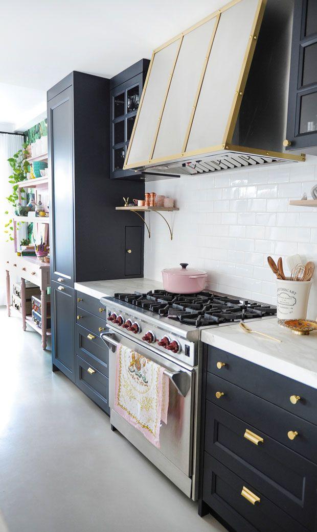 Les bordures et la robinetterie en laiton donnent un côté glamour aux armoires et à la hotte. Entrez à l'intérieur du loft d'une artiste de Vancouver en cliquant ici.
