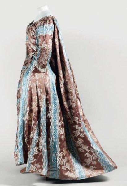 Robe à la française en satin façonné, vers 1760-1770. Lampas liseré à rayures et méandres de fleurs bleu et chocolat. Manteau à larges plis Watteau partant des omoplates, corsage fermé à compères, encolure carrée, manches bouillonnées, parements dits « en platitude » de même étoffe froncée. Jupon complet monté à plis canon et doublé de toiles imprimées, orné sur l'ourlet d'un falbala souligné d'une fine crête de passementerie crème. (soie non fusée, doublure découpée, dos de l'encolure…